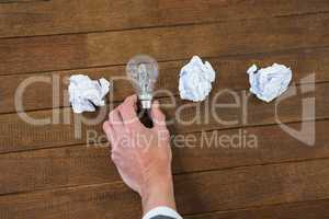 Businessman arranging light bulb with crumbled paper