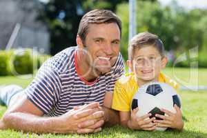 Father and son lying on grass in the park on a sunny day