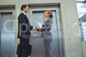 Businesspeople shaking hands near elevator