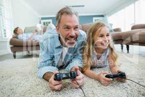 Happy father and daughter playing video game while lying on floor in living room