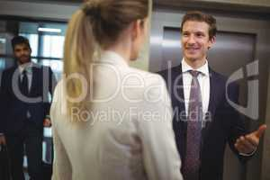 Businessman interacting with his female colleague near elevator