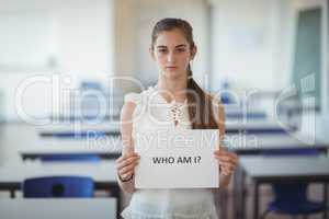 Schoolgirl holding white paper with text sign in classroom