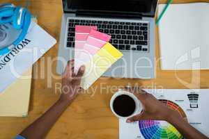 Female graphic designer holding color swatch