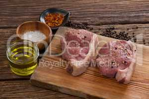 Sirloin chops on wooden board with ingredients