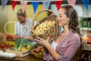 Woman vendor holding a basket if potatoes in grocery store