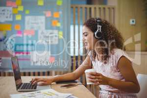 Female graphic designer listening song while using laptop