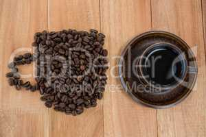Cup of black coffee and coffee beans forming shape of cup
