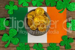 St. Patricks Day pot of chocolate gold coins and irish flag surrounded by shamrock