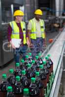 Crate of cold drink bottles moving on the production line