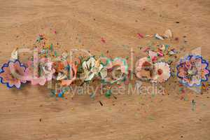 Colored pencil shavings on wooden background