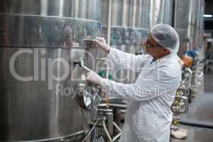 Factory engineer monitoring a pressure gauge of storage tank