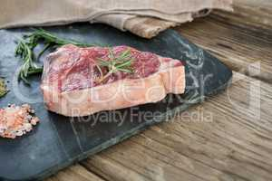 Sirloin chop, rosemary herb and salt on slate board against wooden background