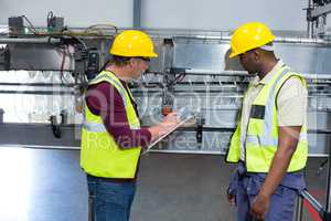 Two factory workers with clipboard working next to production line