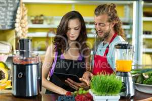 Shop assistants discussing with digital tablet at health grocery shop