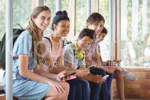 Portrait of happy students sitting on window sill and using mobile phone in corridor