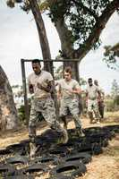 Young military soldiers practicing tyre obstacle course