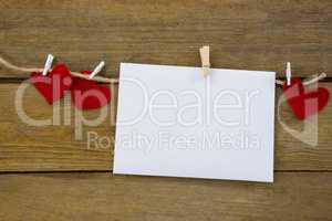 Red hearts and envelope with cloth peg hanging on rope