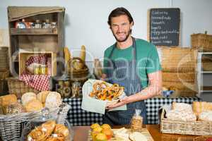 Portrait of male staff holding basket of pretzel at counter