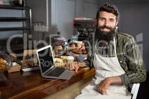 Smiling male staff using laptop at counter in bakery shop