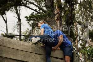 Male trainer assisting woman to climb a wooden wall