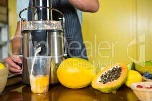 Shop assistant preparing papaya juice