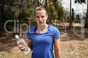 Fit woman holding a water bottle in boot camp