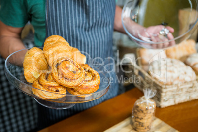 Staff holding tray of croissant at counter