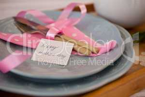 Cutlery, napkin with happy mothers day card on plate