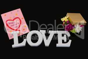 Greeting card, gift box and alphabet love on black background
