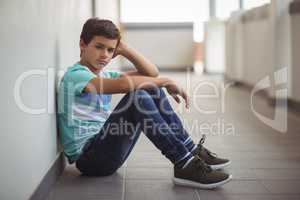 Portrait of sad schoolboy sitting in corridor