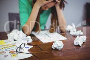 Frustrated female executive sitting with crumpled papers balls