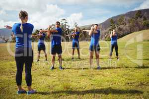 Female trainer giving training to fit people