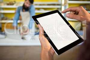 Staff using digital tablet at bakery counter