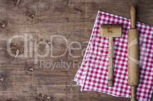 Wooden kitchen items on a red napkin, rolling pin and hammer for
