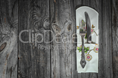 Table knife and fork on gray wooden surface