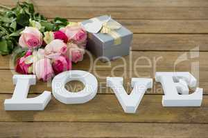 Gift box with bunch of roses and love alphabet on wooden plank