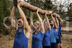 People lifting a heavy wooden log during boot camp