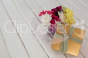 Gift box and bunch of fresh flowers with I love you mom card