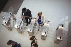 Business executives passing through turnstile gate