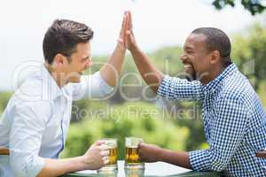 Friends giving high five to each other while having beer