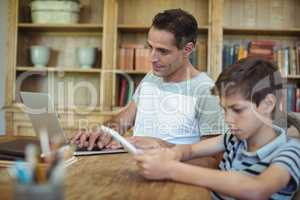 Father and son using laptop and digital tablet in study room