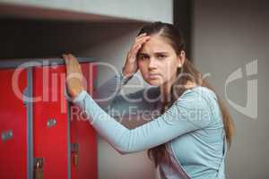 Portrait of sad schoolgirl standing in locker room