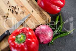 Bell pepper, onion, chillies and knife on wooden board