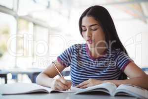 Attentive schoolgirl doing homework in classroom
