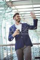 Businessman waving hand while having coffee at railway station
