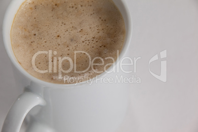 Close-up of white mug of coffee with creamy froth