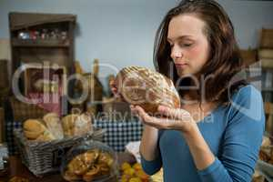 Woman smelling bread at bakery counter