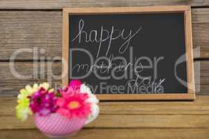 Happy mothers day text written on chalk board with cup of flowers