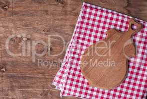 Empty kitchen board for cutting on a brown wooden surface