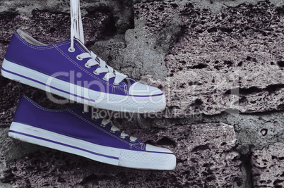 blue sneakers with laces hanging on a brick wall background